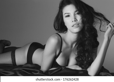 Beautiful asian girl in sexy lingerie posing on bed monochrome