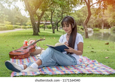 Beautiful Asian girl sitting rest picnic and Listen to music and read books in the park.