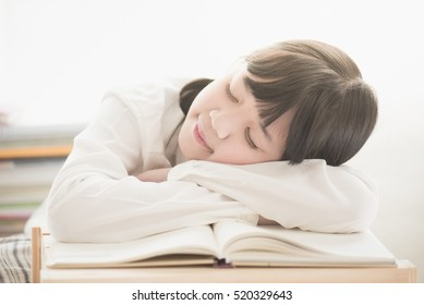 Beautiful Asian girl sleeping on the books