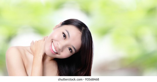 Beautiful asian girl smile touching her shoulders with green background, model is a asian beauty
