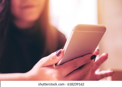 A beautiful Asian girl with smiley face using smart phone in modern cafe
