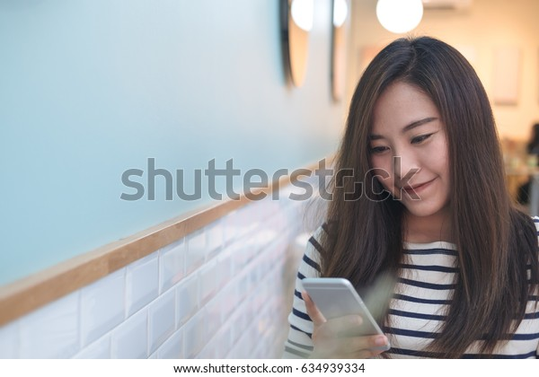 A beautiful Asian girl with smiley face using smart phone in blue modern cafe
