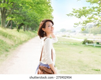 Beautiful Asian girl smiling in the park. healthy new life image.