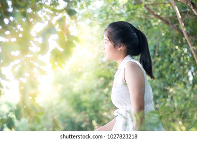 Beautiful Asian girl standing outdoors and looking at camera look happy.