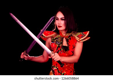 Beautiful Asian girl with swords on black background.
