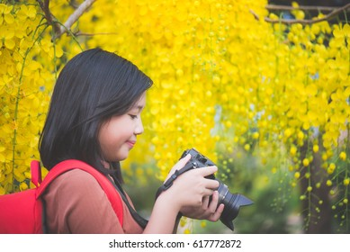 Beautiful Asian girl take photo with blooming yellow flower