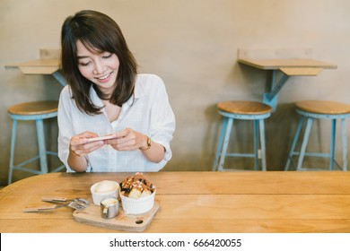 Beautiful Asian girl taking photo of chocolate toast cake, ice-cream, and milk at coffee shop. Dessert or food photograph hobby. Smartphone or mobile phone photography habit concept. With copy space.