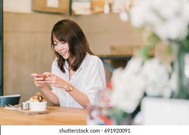 Beautiful Asian girl taking photo of sweet desserts at coffee shop, using smartphone camera, posting on social media. Food photograph hobby casual relax lifestyle, modern social network habit concept