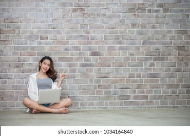 Beautiful asian girl typing on laptop over vintage bricks wall, asian teenage woman sit on the floor and playing computer her finger point up. Education technology university freelance home office e-c