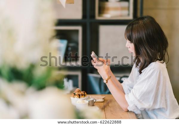 カフェでスマートフォンを使った美しいアジア人の女の子。チョコレートトースト、アイスクリーム、ミルクシロップを添えた。喫茶店のデザート、現代のカジュアルライフスタイルや携帯電話のコンセプト。コピー用スペース付き