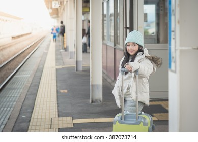 Beautiful Asian girl waiting for train and happy about a journey