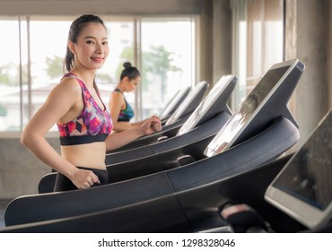 beautiful asian girl is walking on a treadmill in the gym.She Send your eyes with pleasure in exercise because it makes her shapely, the concept of exercise, lose weight, strengthen muscles.