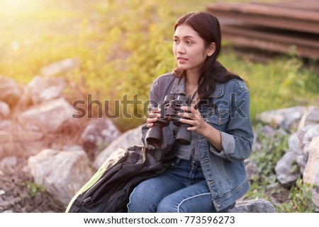 ebe4be4331d Beautiful Asian girl wearing a jeans shirt. She are using binoculars to  look for places