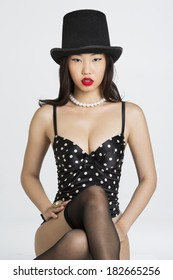 Beautiful Asian girl wearing Top Hat and lingerie against white background