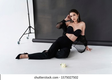 Beautiful Asian girl wearing trousers, a transparent blouse and bra sits on white floor near the gray studio background. Advertising, commercial, fashion design