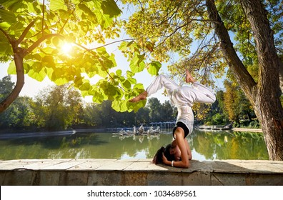 Beautiful Asian girl in white costume doing head stand yoga position in the park