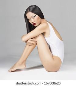 Beautiful Asian girl in white Swimsuit Sitting