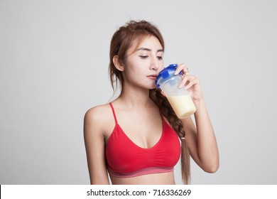 Beautiful Asian healthy girl drinking whey protein on gray background
