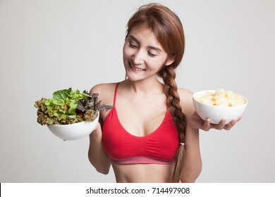 Beautiful Asian healthy girl salad and potato chips on gray background