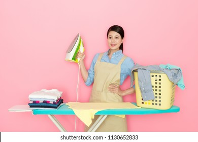 beautiful Asian housewife holding a home ironing on pink blank background