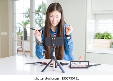 Beautiful Asian influencer woman recording make up tutorial using smartphone camera screaming proud and celebrating victory and success very excited, cheering emotion