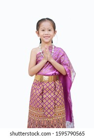Beautiful Asian kid girl in traditional thai dress praying isolated on white background. (Sawasdee is meaning hello).
