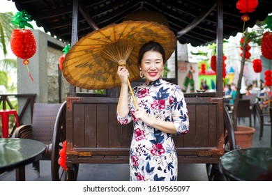 Beautiful Asian lady greeting and holding vintage umbrella in the outdoors.China restaurant outdoor setting.Female wearing qipao.Chinese New Year red lanterns hanging on wooden cart.Waitress on duty.