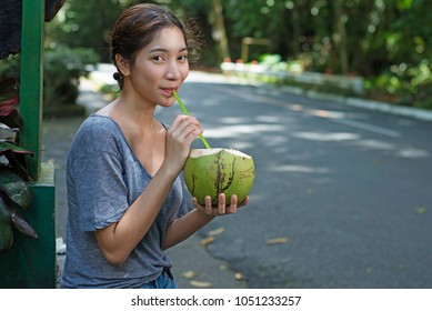 Beautiful asian lady sipping coconut juice with straw.