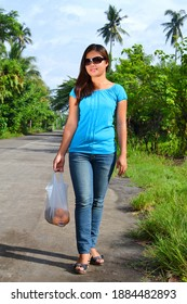 A beautiful Asian lady walking in a countryside with a bag of fresh oranges