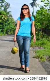 Beautiful Asian lady walking in the countryside with Durian fruit hanged in a rope