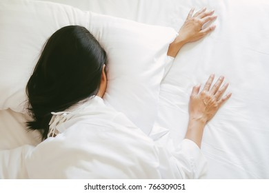 Beautiful asian lazy woman sleeping on the bed with morning light. Relaxing concept.
