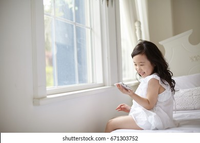 Beautiful asian little girl using tablet while lying on bed