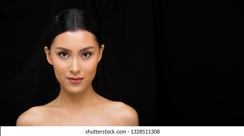 Beautiful Asian Long straight black wrapped hair tan skin woman in open shoulder, clean look fashion make up, studio lighting dark fabric bokeh background empty copy space text logo