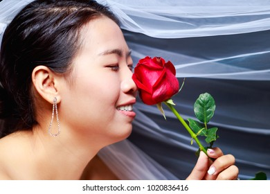 Beautiful Asian look woman in white wedding dress holding red rose flower on black background, Bride theme portrait, selected focus