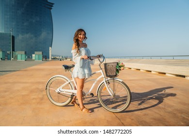 Beautiful Asian model in a blue dress rides a white bicycle in a modern city with business building on background. Concert of travel, business and health
