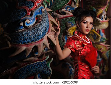 Beautiful asian model wearing a red chinese tradition dress standing near the dragon pole in the old shrine