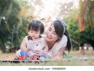 Beautiful asian mom and baby playing toy  happiness in the park , outdoor