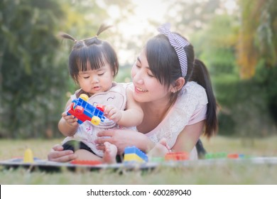 Beautiful asian mom and baby playing with toy, happiness in the park outdoors, mother's day