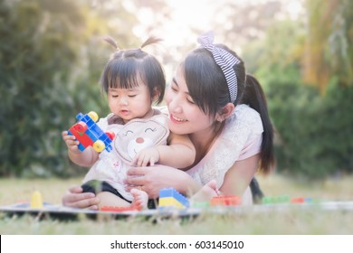 Beautiful asian mom and baby playing toy  happiness in the park , outdoor ,mother day