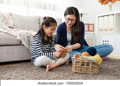 beautiful Asian mom teaches her daughter how to knitting for the autumn sweater for cold season is coming in the living room at home