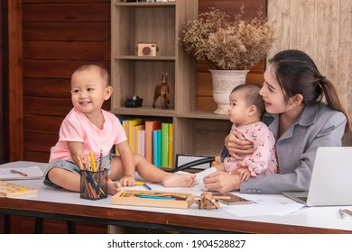 Beautiful Asian mother confuse multi task while work at home, women work from home fussy taking care children in quarantine social distance during Covid-19 crisis, worried single mom with chaotic kids