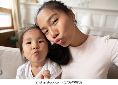 Beautiful asian mother and her little cute daughter taking selfie photography on gadget sending kisses making funny faces, webcam close up portrait view. Fun activity, modern tech young family concept