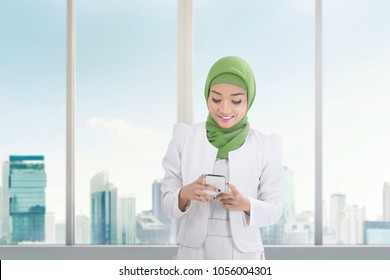 Beautiful asian muslim woman with mobile phone inside the building