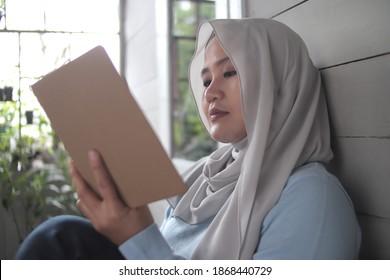 Schöne asiatische Muslimfrau, die ihr Buch liest, während sie außerhalb ihres Hauses sitzt, genießt Mädchen ihre Zeit durch Freizeitaktivitäten, fröhlichen, fröhlichen Ausdruck
