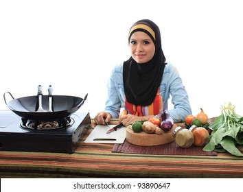 Beautiful asian muslim woman smile while looking to the camera in the kitchen isolated white background