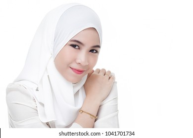 beautiful asian muslim woman wearing white shirt and white hijab posing on table isolated on white background.closeup.