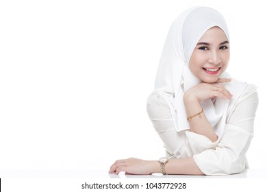 beautiful asian muslim woman wearing white shirt and white hijab posing on table isolated on white background.copy space