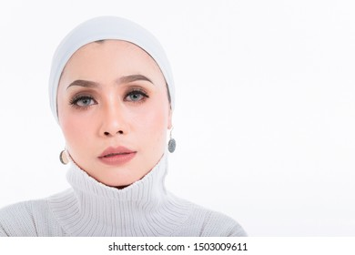 Beautiful asian muslim woman wearing white shirt and white hijab posing on table with closeup shoot isolated on white background. copy space.