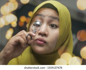 Beautiful Asian muslim woman wearing hijab and applying makeup. Beautiful girl looking in the mirror and curl her eyelash with eye lash curler