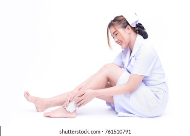 Beautiful Asian nurse get injured or painful and touching her ankle on Achilles tendon area (joint tarsal  bone pain or muscle pain concept) while using gauze or adhesive plaster over ankle